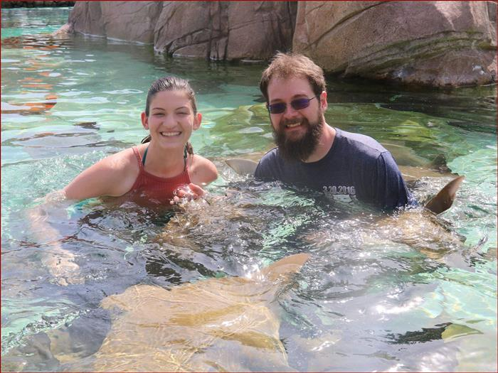 Photo of Mrs. Burghard & her husband swimming with stingrays.