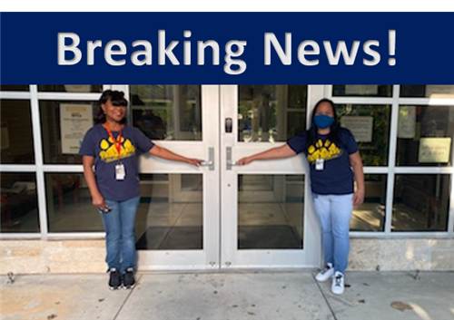 Mrs. Johnson and Mrs. Manzano in front of the entrance doors to the school.